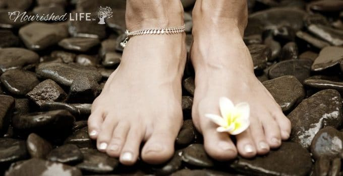 Young woman's feet standing on black natural stones and holding a small yellow flower between the toes.